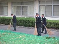 銀杏を箒で掃く生徒たち